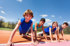 Happy teenagers holding plank outdoor on the track. Close-up picture of four happy teenagers in sportswear holding a plank standing in a row  on the track Royalty Free Stock Photography