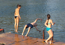 Happy teenagers jumping into the river. Teenage boy and teenage girls jumping into the river from old dock Stock Images