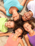 Happy teenagers lying on a sandy beach. In a circle Stock Photo