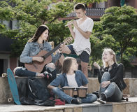 Happy teenagers musicians in park. Company of happy teenagers musicians with instruments in park on summer day Stock Photos
