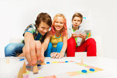 Happy teenagers play table game together at home Royalty Free Stock Photography