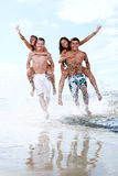 Happy teenagers playing at the sea royalty free stock photography