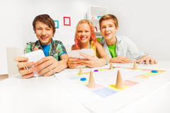 Happy teenagers playing table game holding cards. And sitting on white sofa and table at home Royalty Free Stock Images