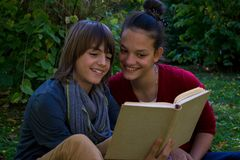 Happy teenagers reading a book in the park. stock photos