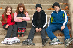 Happy teenagers in roller skates sitting outdoor. Group of happy teenagers in roller skates sitting on the stairs royalty free stock photography