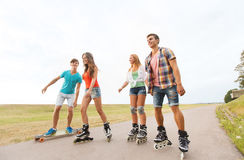 Happy teenagers with rollerblades and longboards Royalty Free Stock Photography