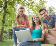 Happy teenagers using a laptop at the park Royalty Free Stock Photography