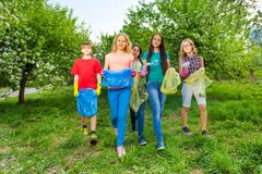 Happy teenagers wear gloves and carry garbage bags. Walking together cleaning the garden royalty free stock images