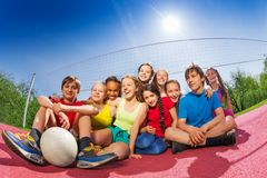 Happy teenagers who sit on volleyball game court. Holding ball during summer sunny day Stock Photos