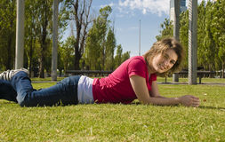 Happy teenger. Happy teenager lying on the grass, smiling in the sun Royalty Free Stock Photos