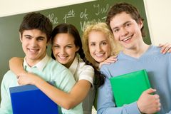 Happy teens. Portrait of happy students standing next to each other and looking at camera with smiles Royalty Free Stock Photography