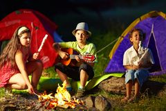 Happy teens around night campfire Royalty Free Stock Image