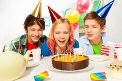 Happy teens celebrate birthday girl blow candles. Group of boys and girls on birthday party blowing cake candles, presents balloons and decorations around Stock Photo