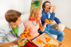 Happy teens eating pizza pieces together at home Royalty Free Stock Photography
