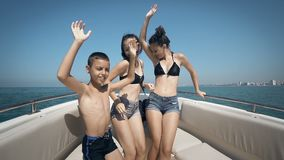 Happy teens are having the time of their lives dancing on a boat