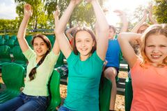 Happy teens hold arms up during game on tribune. Happy teens hold arms up during game at the stadium sitting on the tribune outside in summer Royalty Free Stock Photography