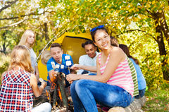 Happy teens hold marshmallow sitting on campsite Royalty Free Stock Images