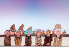 Happy teens with long healthy hair laying upside down. Stock Image