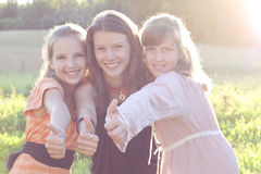 Happy teens outdoors. Happy girls with thumbs up. Low contrast and lens blures royalty free stock photos