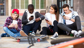 Happy teens playing on smarthphones Royalty Free Stock Photos