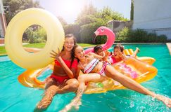 Happy teens playing with swimming floats in pool royalty free stock photography