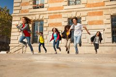 Happy teens running after classes at sunny day. Happy teenage boys and girls running from college building after classes Stock Photo