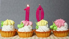 Happy ten birthday, pink number candles burning on cupcakes