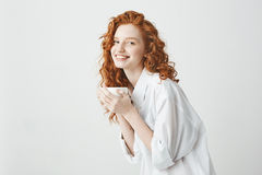 Happy tender redhead girl in shirt smiling holding cup looking at camera sitting on table. White background. Stock Image