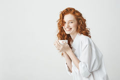 Happy tender redhead girl in shirt smiling holding cup looking at camera sitting on table. White background. Happy young tender redhead girl in shirt smiling Royalty Free Stock Image