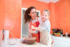 Happy child whipping chocolate with mother Royalty Free Stock Photos
