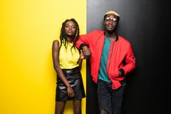Happy tender young couple smiling and have fun over colorful background. Afro american man and woman isolated on yellow and black stock photos