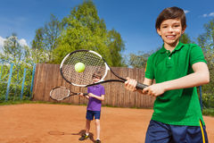 Happy tennis player with his partner at the court. Portrait of happy tennis player, kid boy hitting forehand and his partner behind him on the tennis court Stock Photos