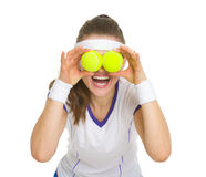 Happy tennis player holding balls in front of eyes Stock Photo