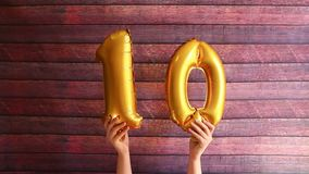 Happy tenth birthday, golden air balloons with number ten, anniversary. Happy tenth birthday, golden air balloons with number ten on wooden background stock footage