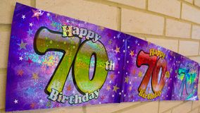 Happy 70th Birthday banner on wall. Happy 70th Birthday banner in purple Stock Photography