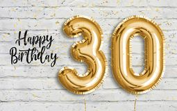 Happy 30 th birthday gold foil balloon greeting white wall background.