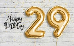 Happy 29 th birthday gold foil balloon greeting white wall background.