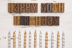 Happy 30th Birthday Spelled in Type Set. On a distressed wooden table Stock Photos