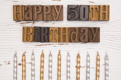 Happy 50th Birthday Spelled in Type Set. On a distressed wooden table Stock Photography