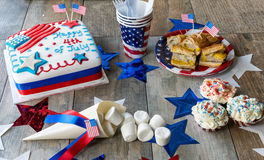 Happy 4th of July cake with cupcakes, marshmallows and hot dogs Royalty Free Stock Images