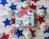 Happy 4th of July cake with cupcakes seen from above. Happy 4th of July cake with cupcakes on white, wooden surface, seen from above royalty free stock photography