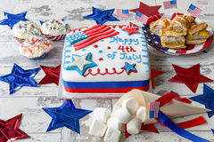 Happy 4th of July cake with marshmallows and cupcakes. Happy 4th of July cake with marshmallows, cupcakes and sausage rolls stock photos