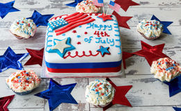 Happy 4th of July cake surrounded by cupcakes. On white, wooden surface stock photography