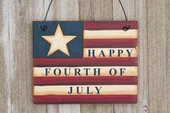Happy 4th of July greeting. Happy 4th of July text on a retro USA flag wood sign on weathered wood royalty free stock images