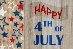 Happy 4th of July greeting. Happy 4th of July text with USA red, white and blue stars burlap ribbon on weathered wood royalty free stock photos