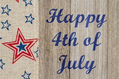 Happy 4th of July greeting. Happy 4th of July text with USA red and blue stars burlap ribbon on weathered wood royalty free stock images