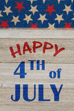 Happy 4th of July greeting. Happy 4th of July text with USA red and blue stars burlap ribbon on weathered wood royalty free stock photo