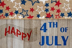 Happy 4th of July greeting. Happy 4th of July text with USA red, white and blue stars burlap ribbon on weathered wood stock photos