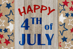 Happy 4th of July greeting. Happy 4th of July text with USA red, white and blue stars burlap ribbon on weathered wood stock photography