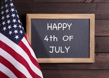 HAPPY 4th OF JULY Sign and the American Flag. American flag and HAPPY 4th OF JULY written on a chalkboard on a rustic wooden background royalty free stock photo